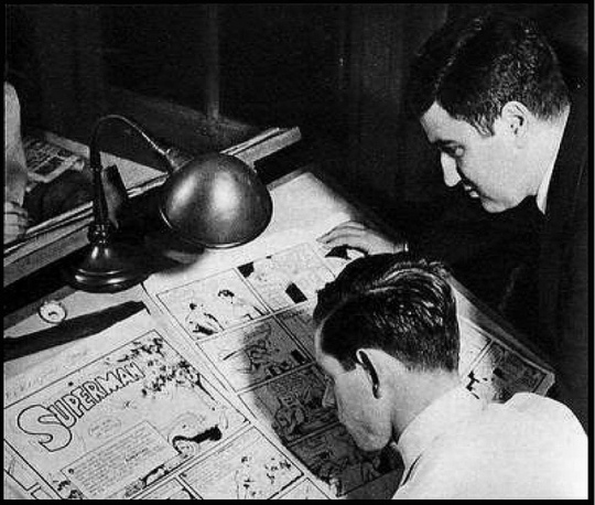Joe Shuster drawing as Jerry Siegel watches. Shuster held his face close to the paper because his extremely poor eyesight necessitated it.